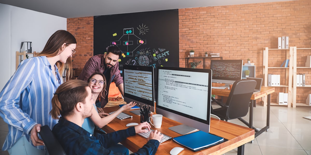 Four programmers sit in an office around a computer, studying object oriented programming.