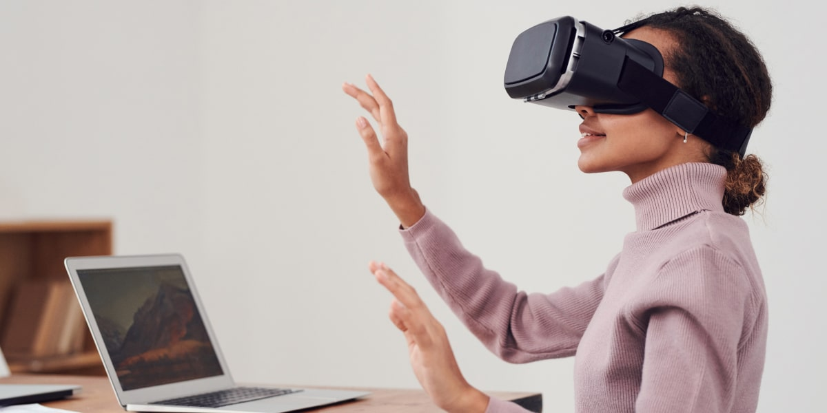 A UX designer standing in an office, wearing a VR headset