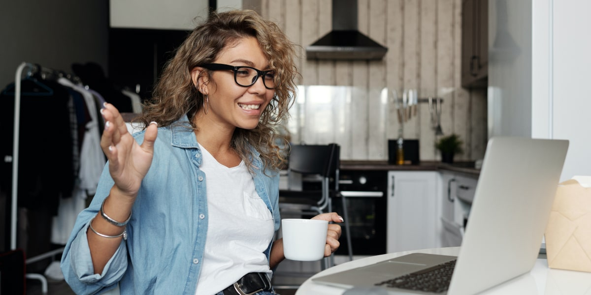 A marketing pro turned UX designer, working from home with her laptop and a cup of coffee