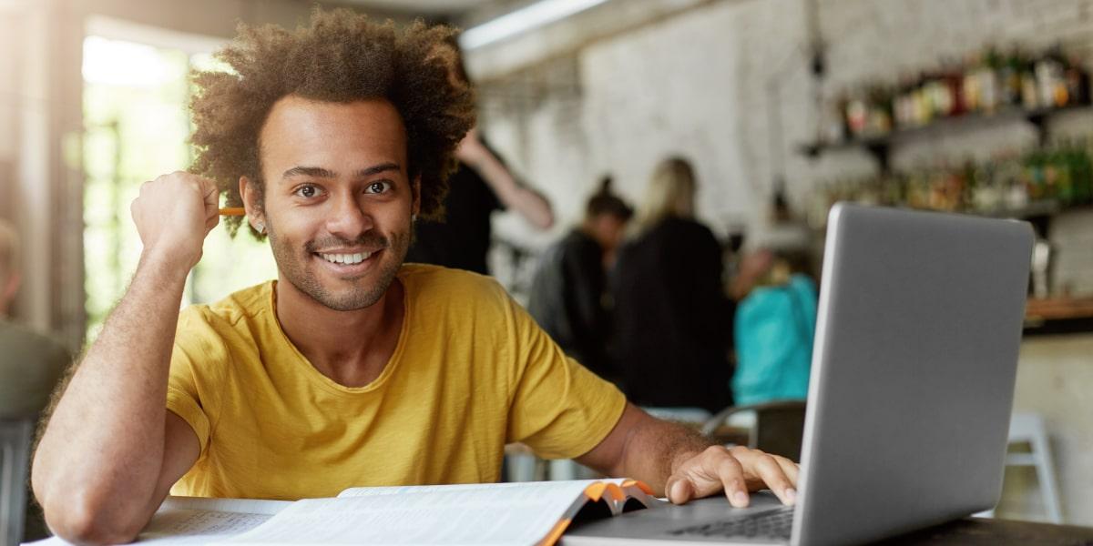 A UI designer sitting at a computer, smiling