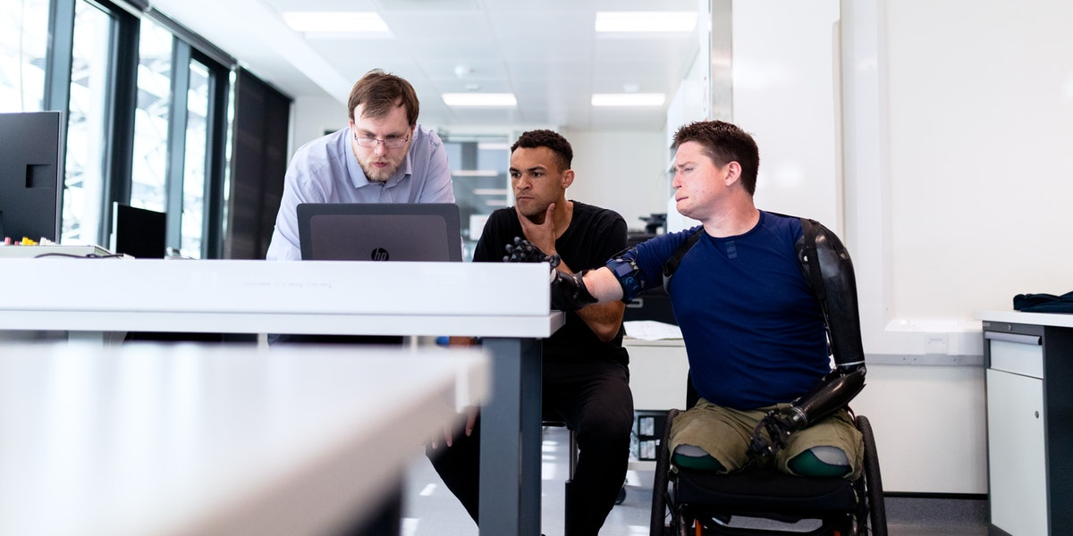 Three men sit around a screen, one in a wheelchair, to learn web development.