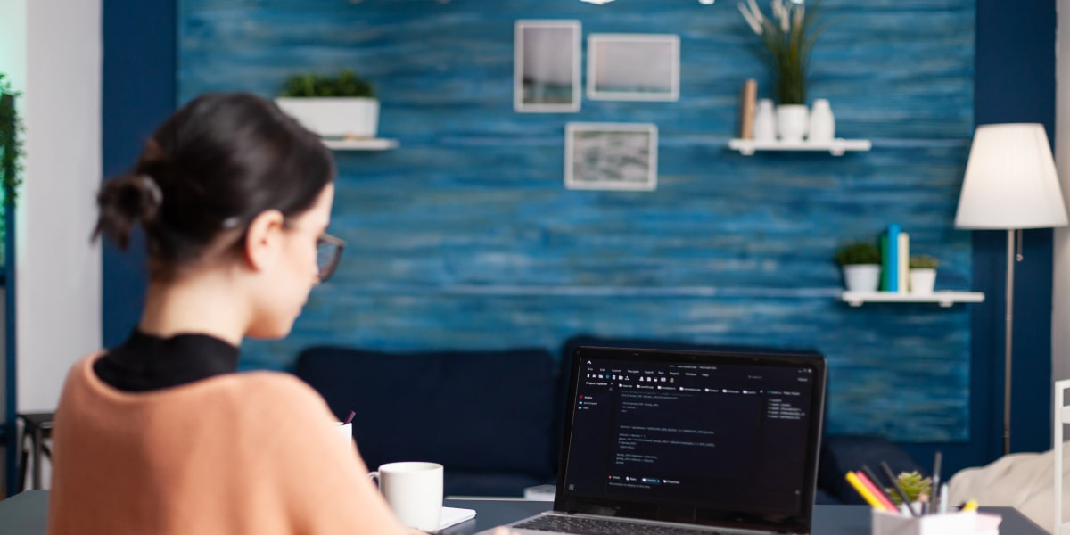 Female JavaScript developer sits at a desk in a startup office, coding on a laptop.