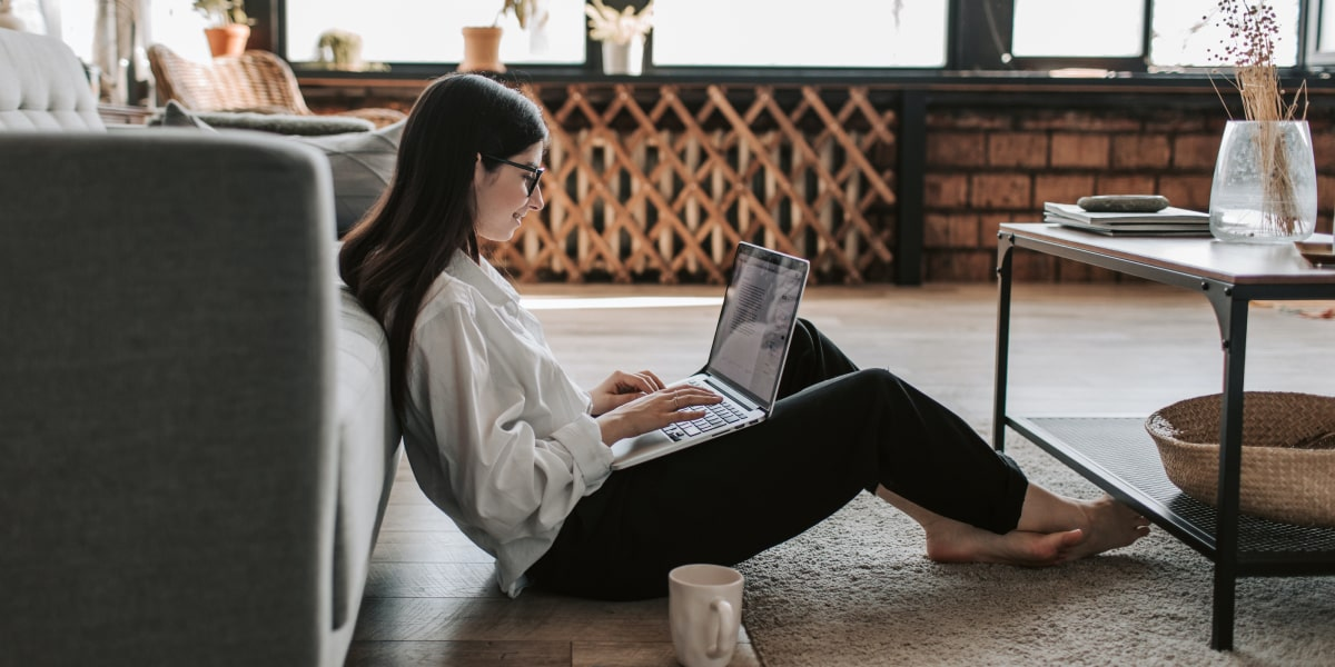 An aspiring designer sitting on the floor in their living room with a laptop and cup of coffee