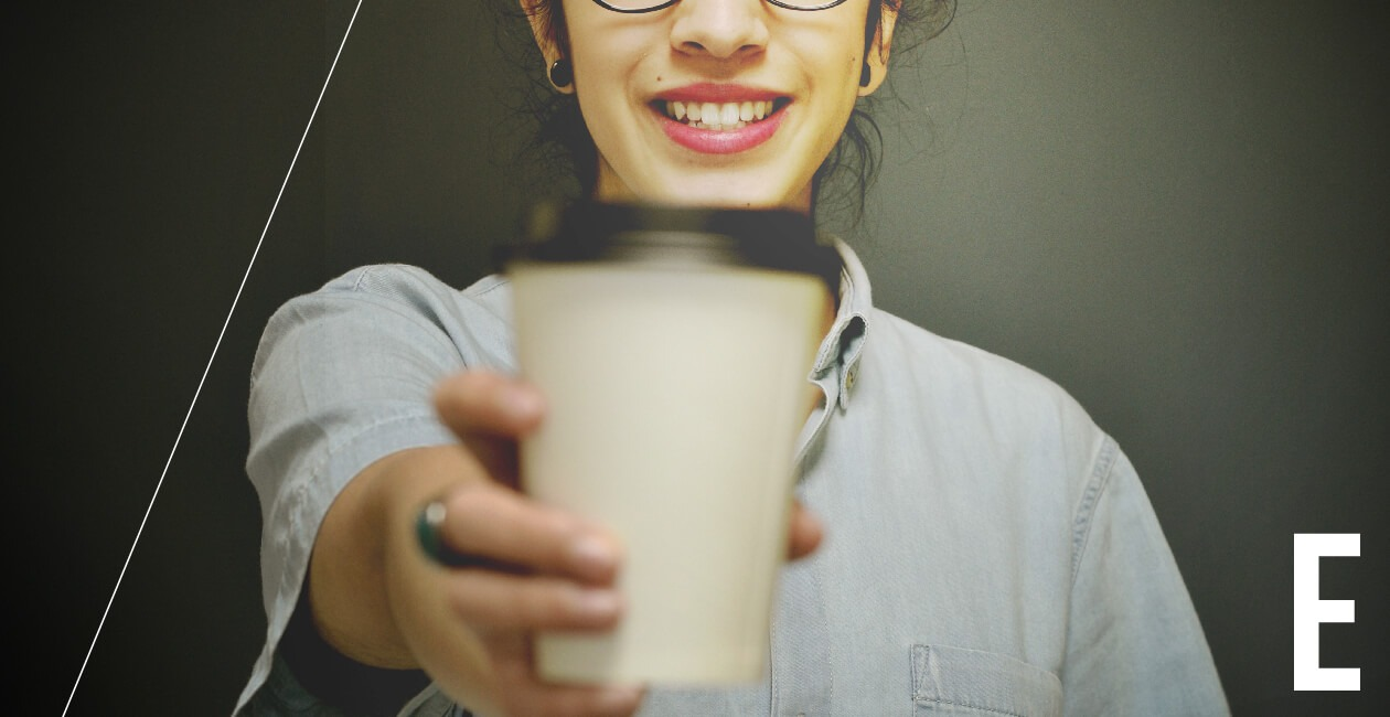 A person offering a cup of coffee toward the camera