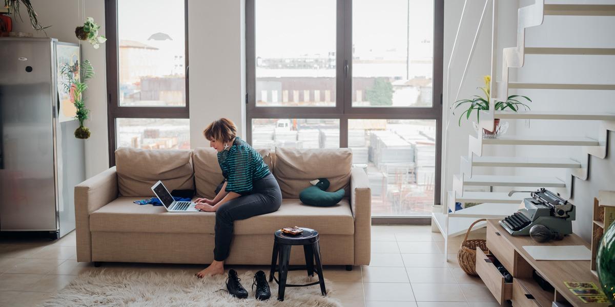 An aspiring UI designer sitting on a sofa, working on a laptop