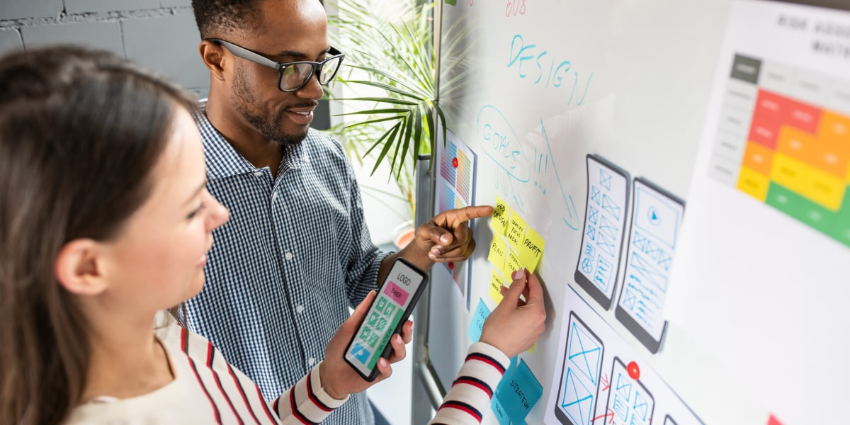 Two UX designers working at a whiteboard