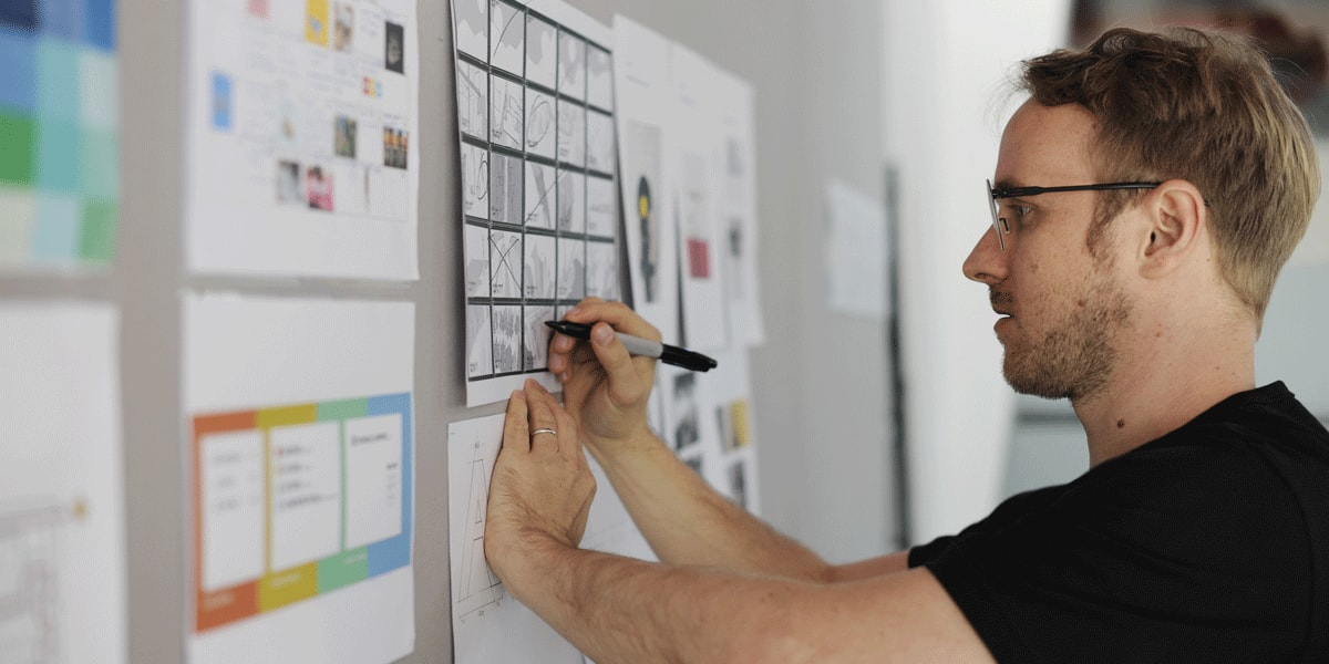 A designer in side profile, writing on a whiteboard