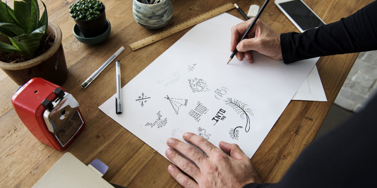 A designer sketching on a piece of paper