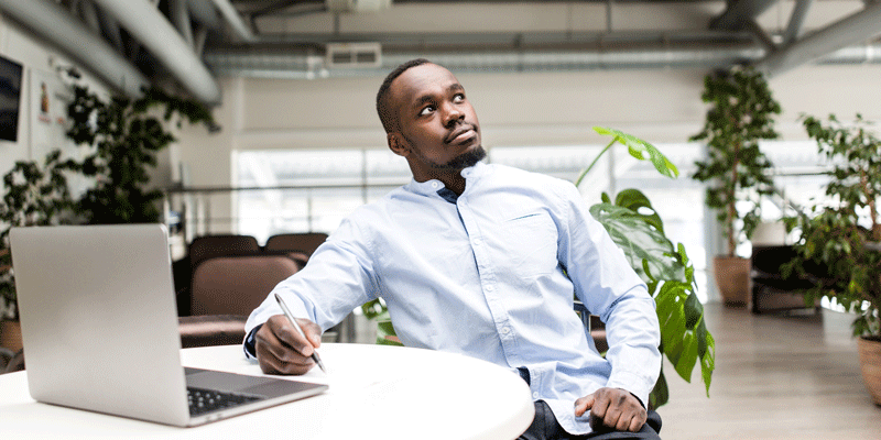 Designer sitting at a desk in an office, staring off thoughtfully
