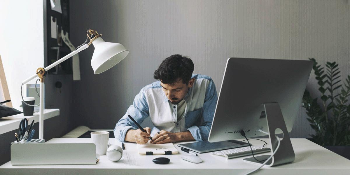 An aspiring UI designer sitting at a desk, writing in a notebook