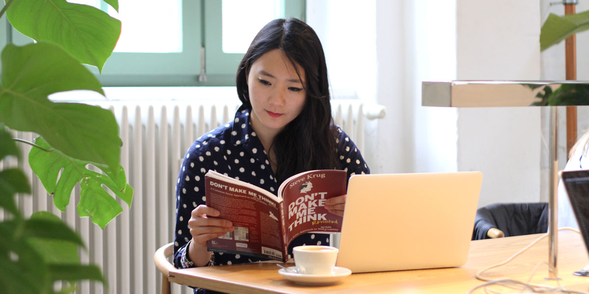 An aspiring designer ditting at a table with a laptop and cup of coffee, reading Krug's book (titled Don't Make Me Think)
