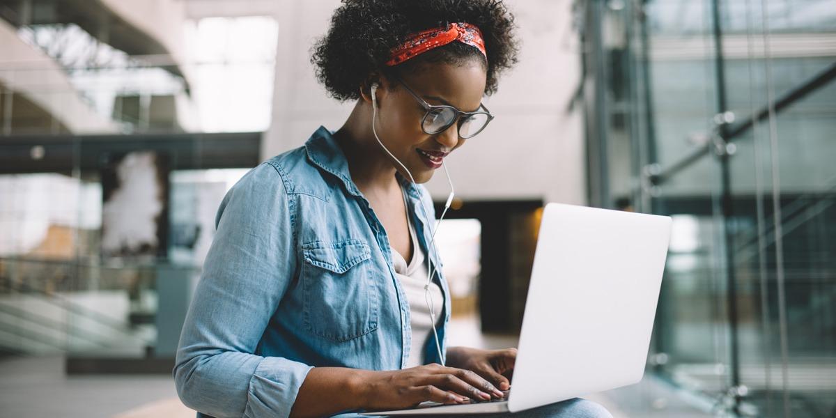 An aspiring UX designer wearing headphones and working on a laptop
