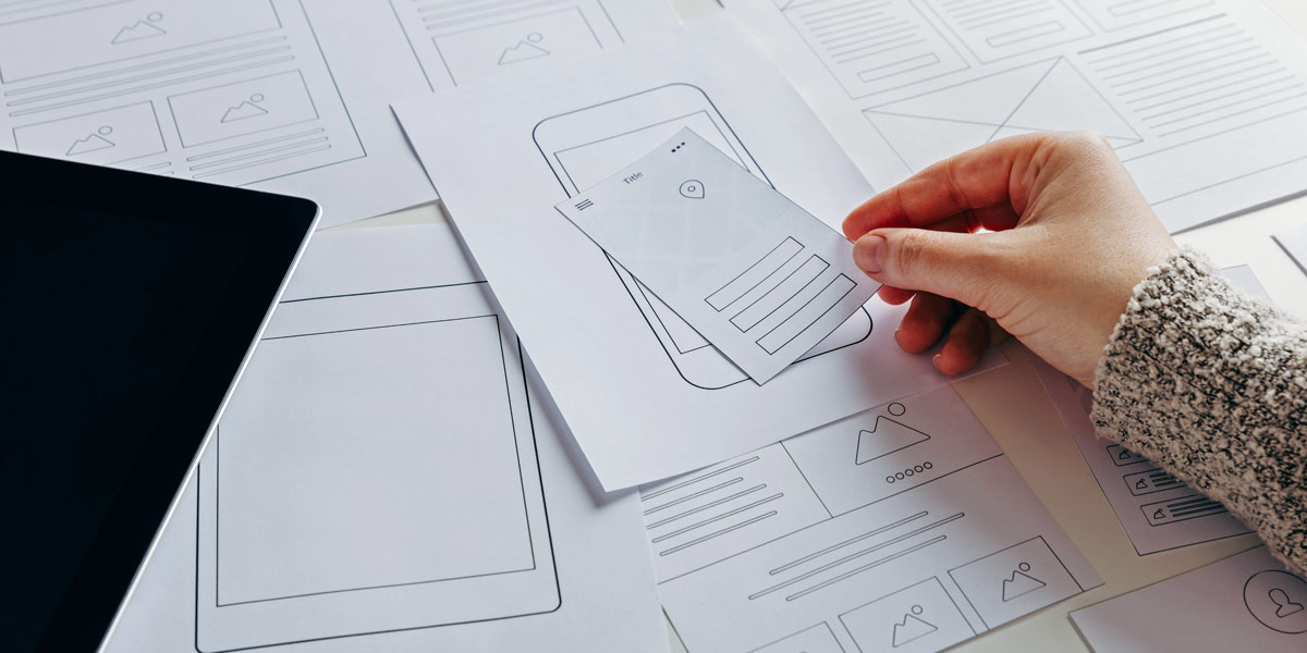 A designer's hand, rearranging parts of a paper prototype