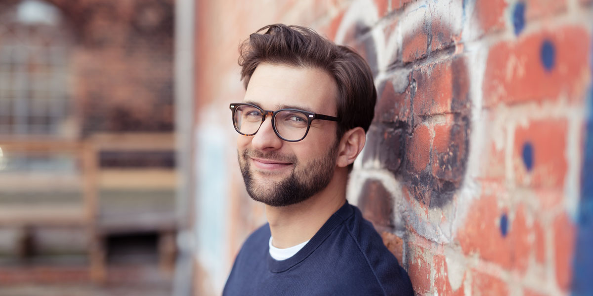 A web developer leaning up against a brick wall.