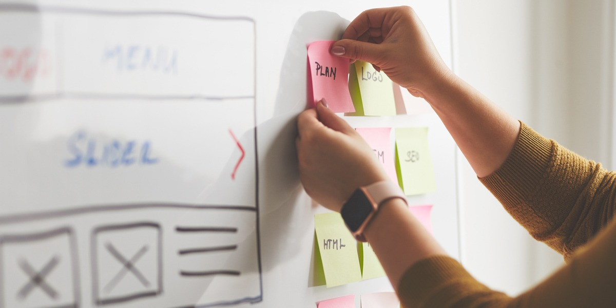 Close-up of a UX strategist's hands putting a sticky note on a whiteboard outline of a project