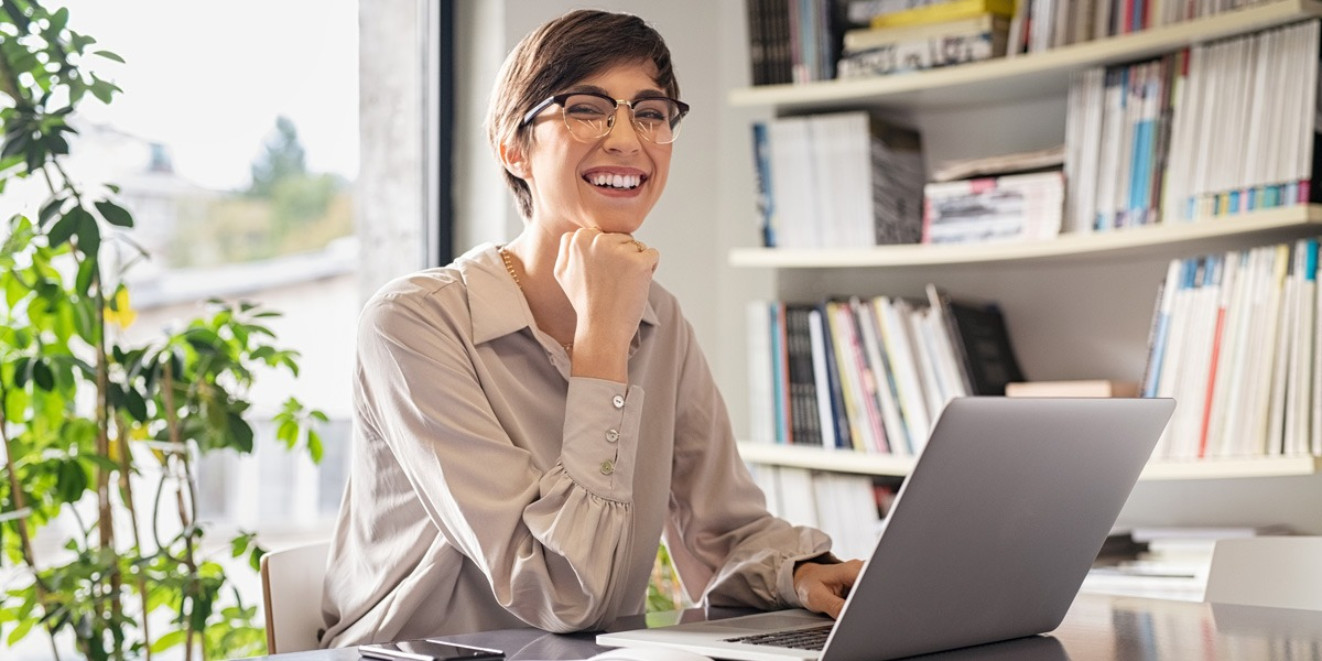 A data analyst sitting at a desk, smiling