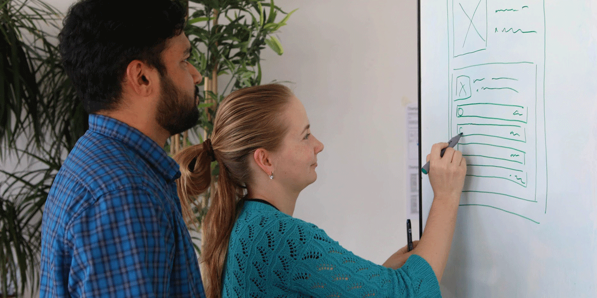 A UX researcher and web developer looking at a whiteboard mockup