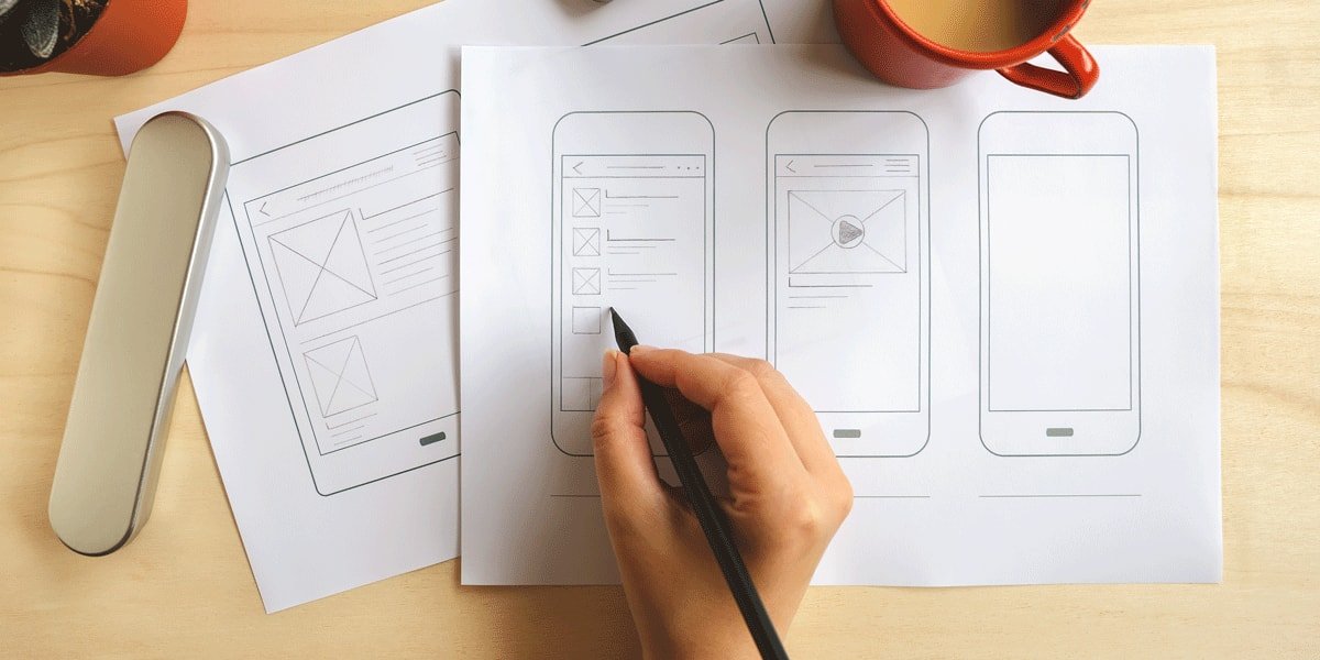 A UX designer's hands doing wireframing on paper