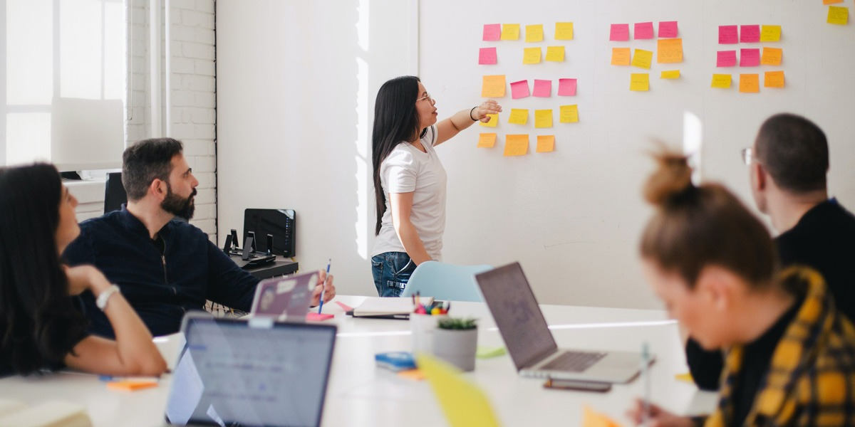 A group of product designers meeting to create an affinity map on a whiteboard with sticky notes