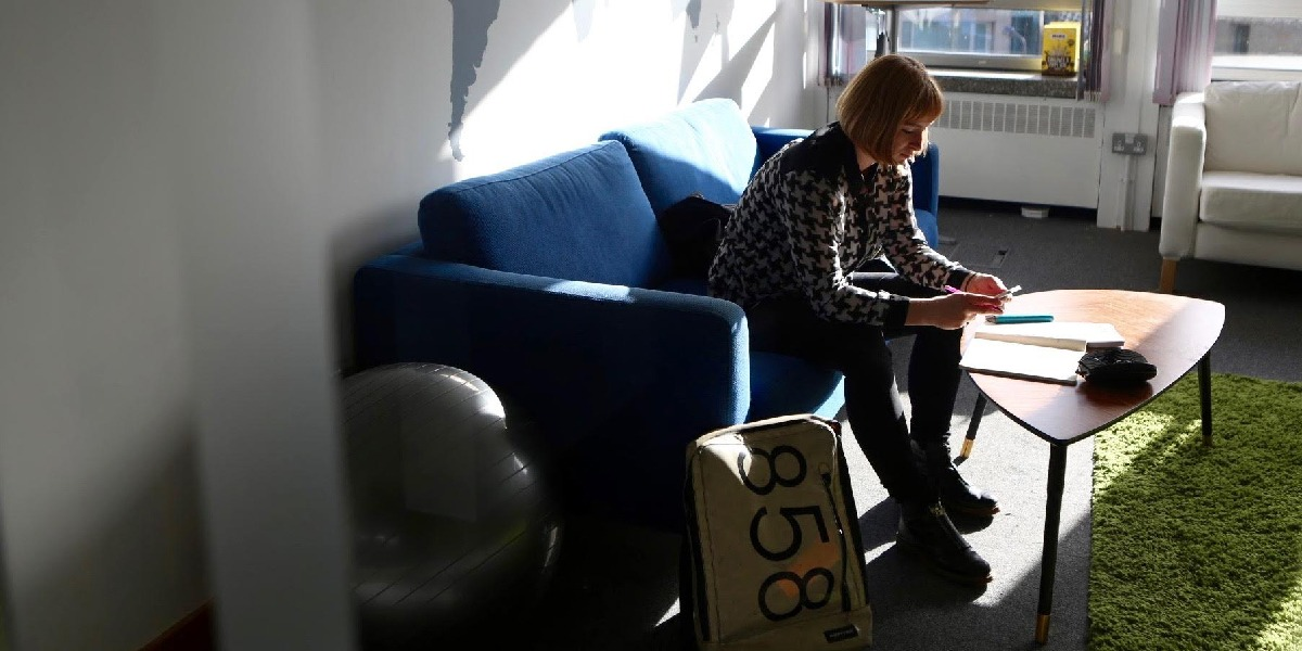 A person sitting on a couch in a sunlit room, doing something on their phone