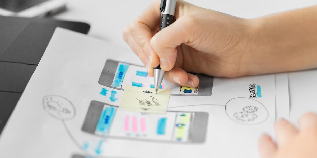 A UI designer sketching out wireframes for a website