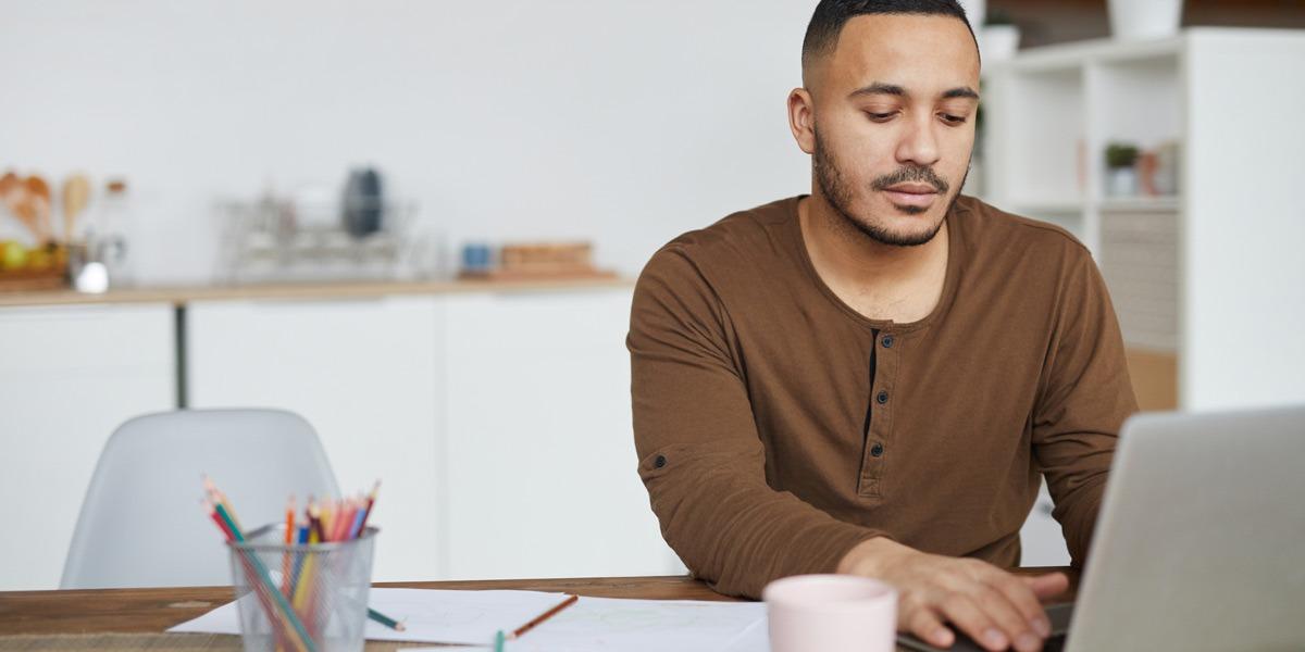 An aspiring UX designer working at a laptop in their kitchen