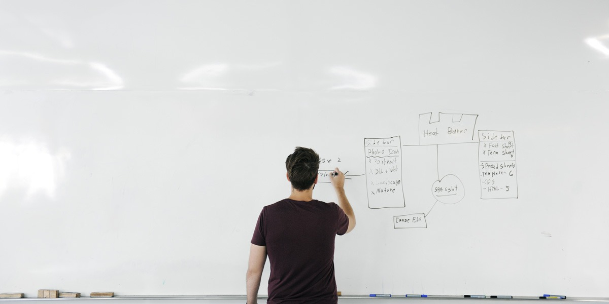 A new uUX designer standing at a whiteboard, drawing wireframes with their back to the camera