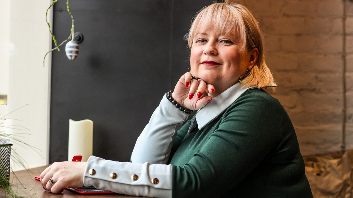 An spiriting UX designer sitting at a desk, smiling at the camera
