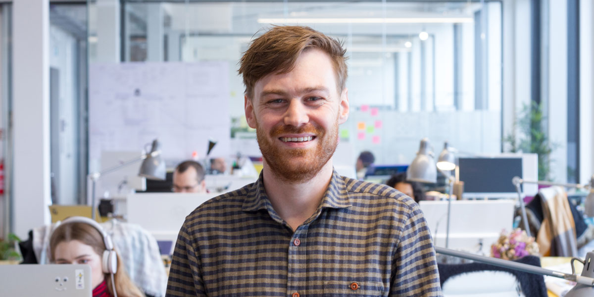 A qualified web developer smiles at the camera in a startup office.