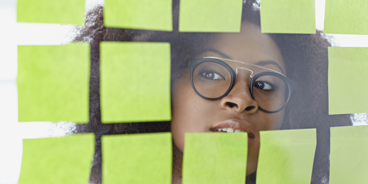A UX designer peeking through a glas wall covered in sticky notes