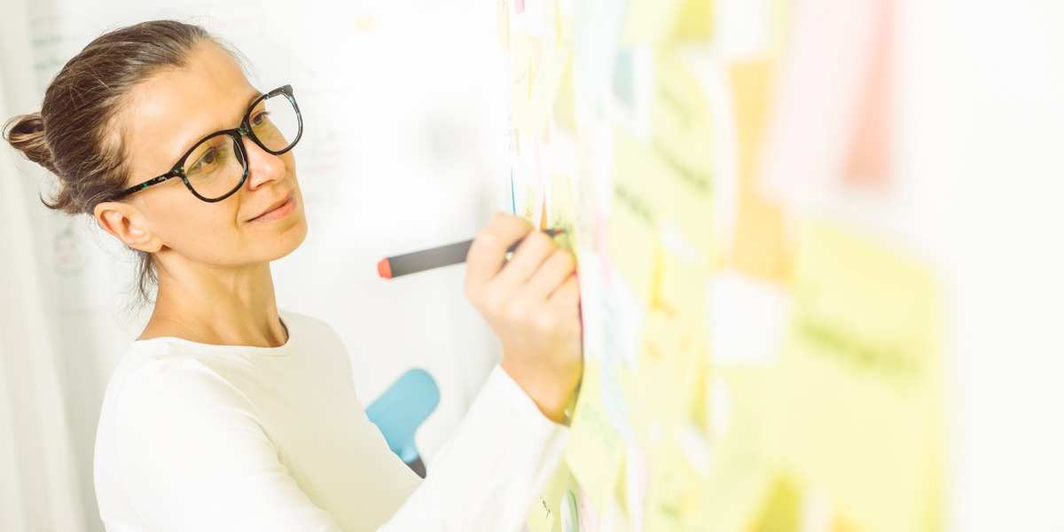 A designer writing notes on a whiteboard