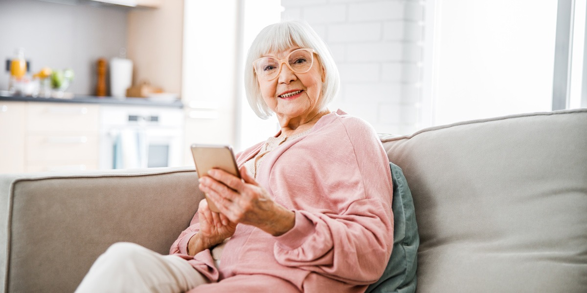 A woman sitting on her couch, holding a mobile phone and smiling at the camera