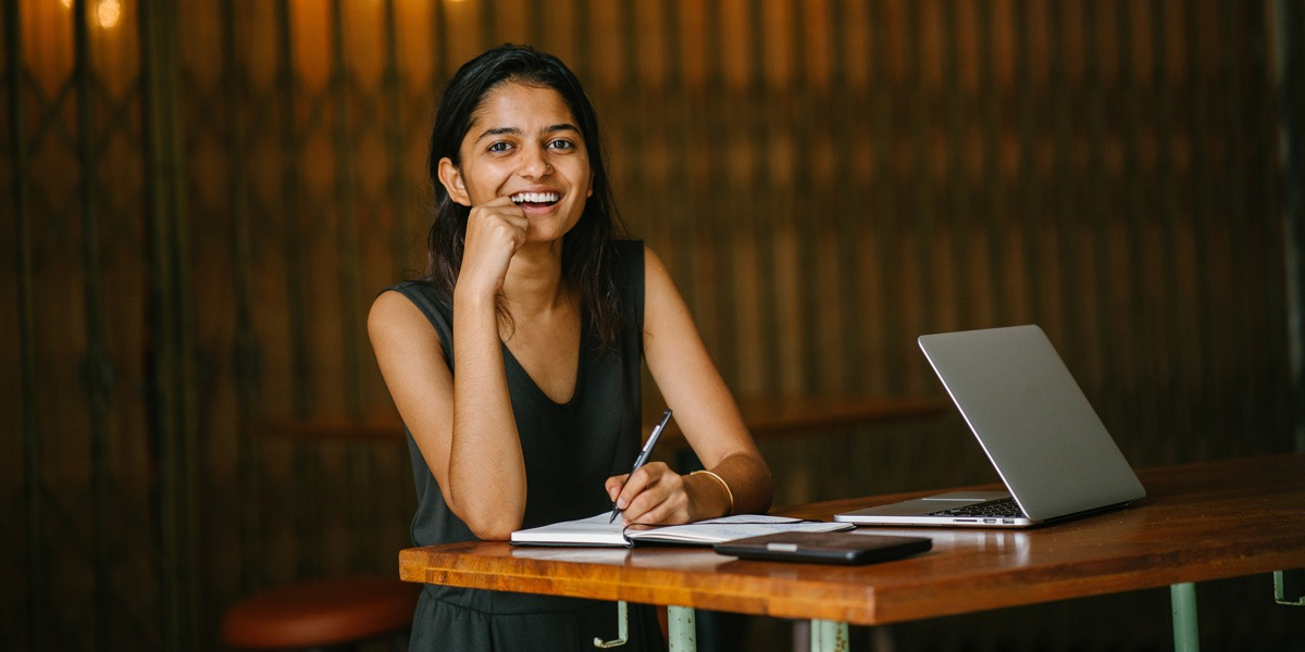 A data analyst writing in a notebook, smiling