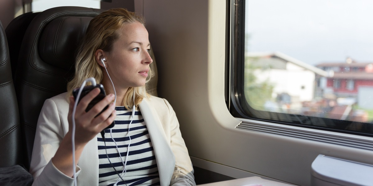 A woman sitting on a train, looking out the window with earphones in, listening to something on her phone