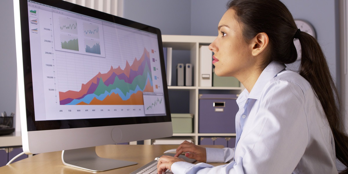 A data analyst in side profile, looking at data visualizations on a screen