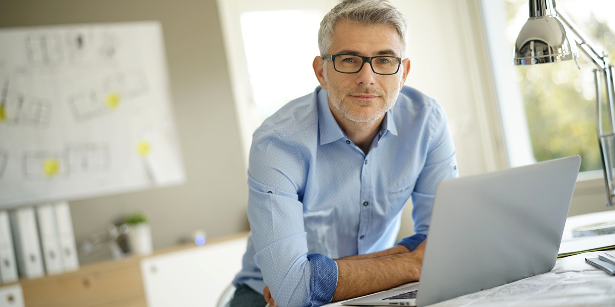 A designer smiling, sitting at a desk with a laptop