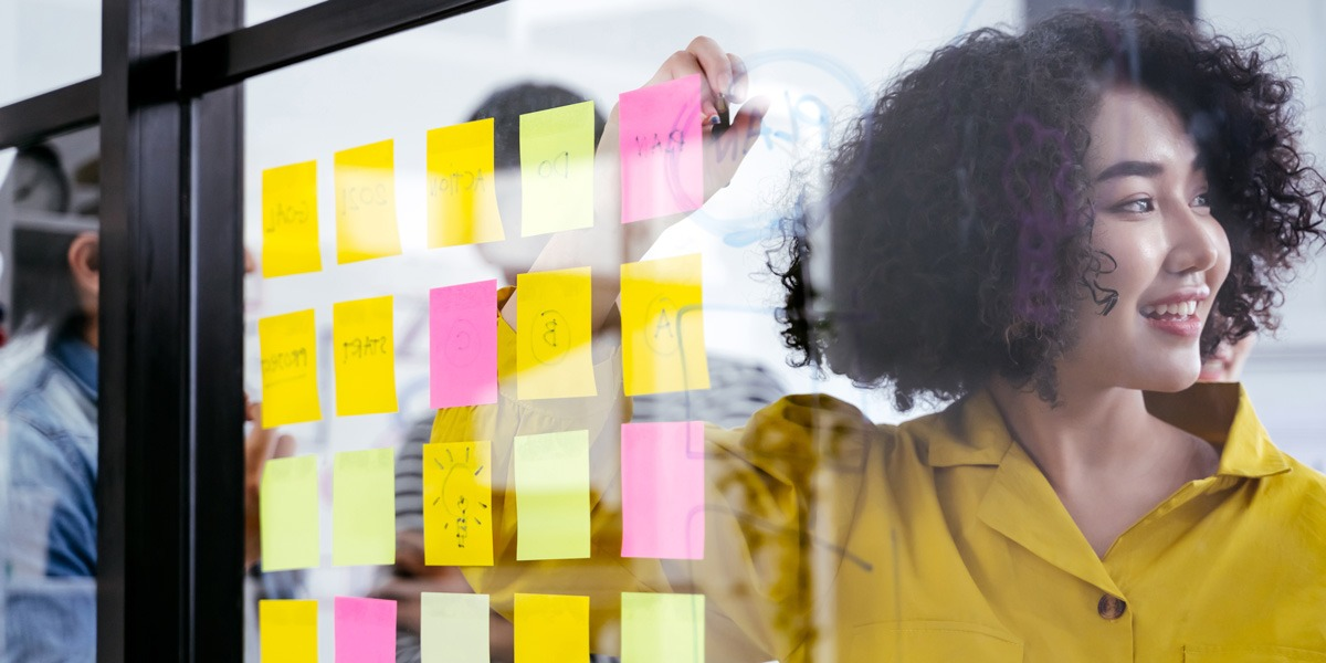 Designer standing behind a glass wall covered in sticky notes