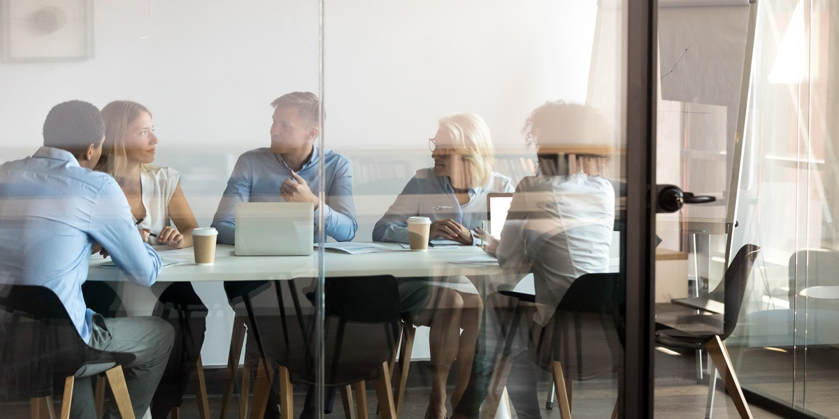 A group of data analysts sitting in a glass meeting room