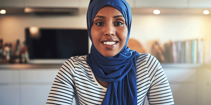 A web developer in a headscarf working from home looks at the camera.
