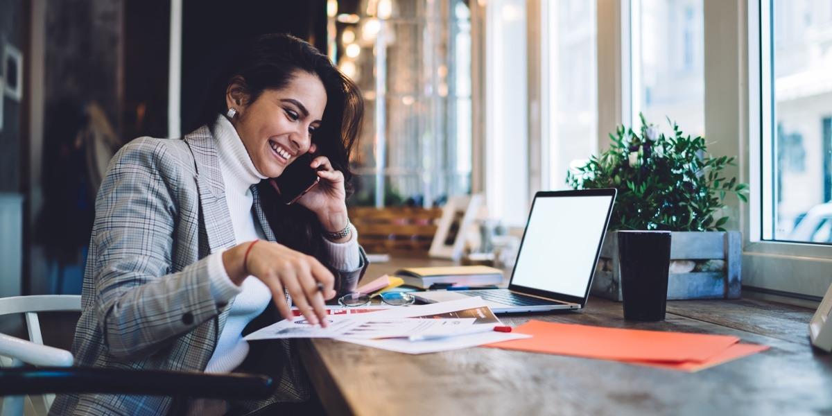 An aspiring designer sitting at a desk, talking on the phone