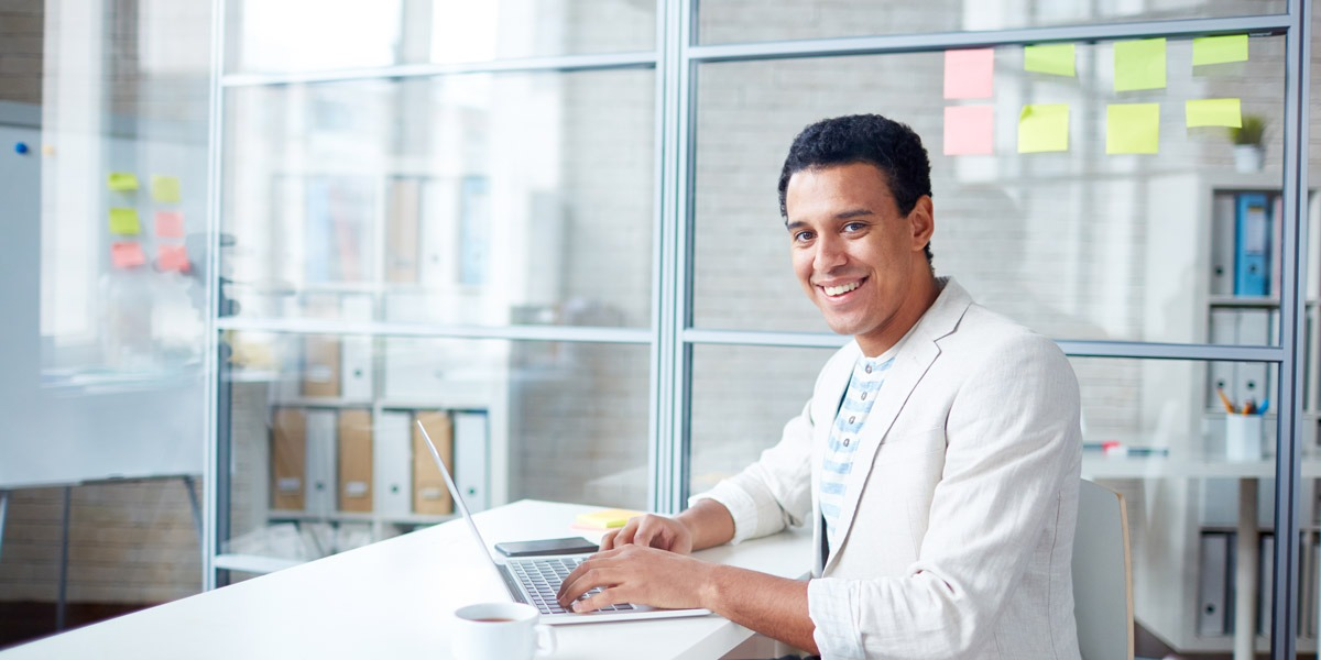A designer sitting in a bright office, smiling