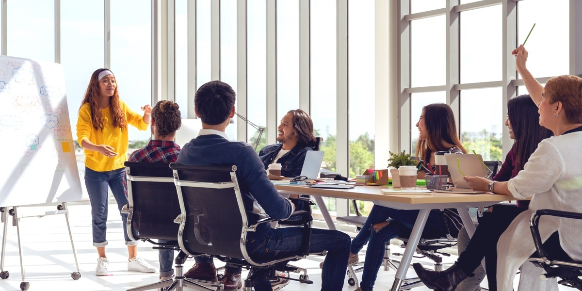 A group of product designers sitting around a table in a sunny office