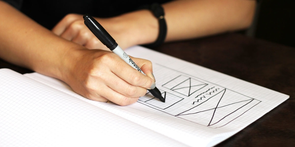 UX designer's hands drawing a simple wireframe on paper