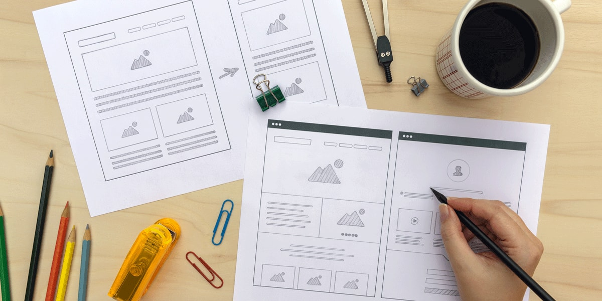 A designer's hands, adding detail to a paper wireframe