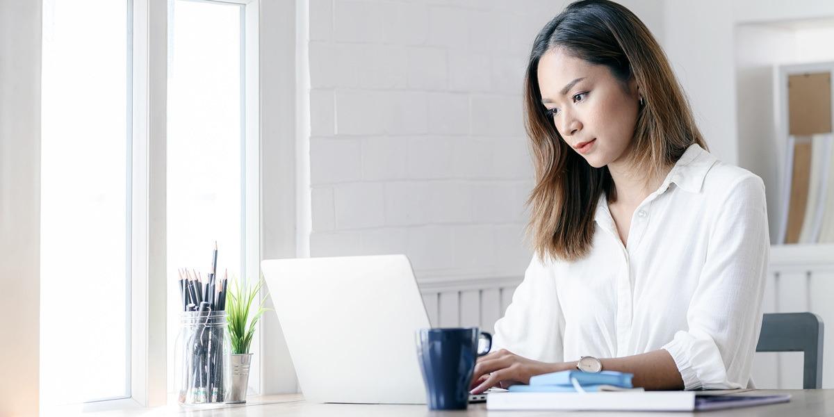An aspiring data analyst typing on a laptop keyboard