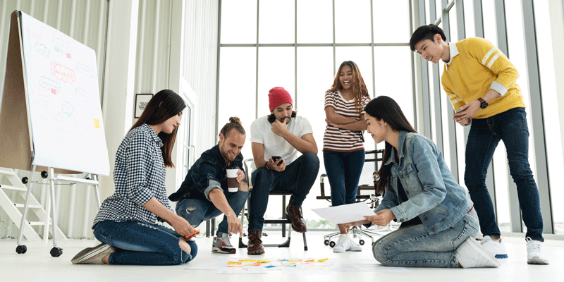 A group of designers gathered around a collection of ideas spread out on the floor