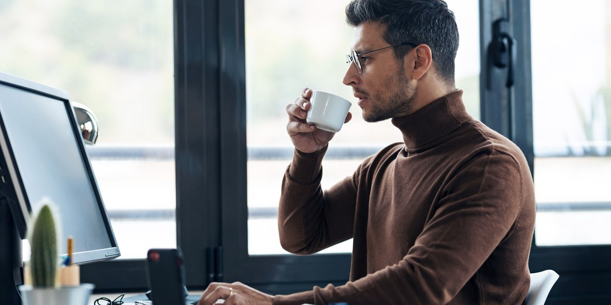A data analyst in side profile, sipping a cup of tea, looking at a computer screen