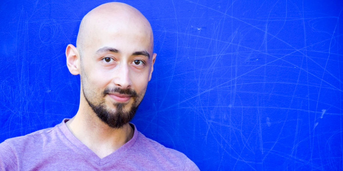 Radi, a Berlin-based data analyst, standing against a blue background