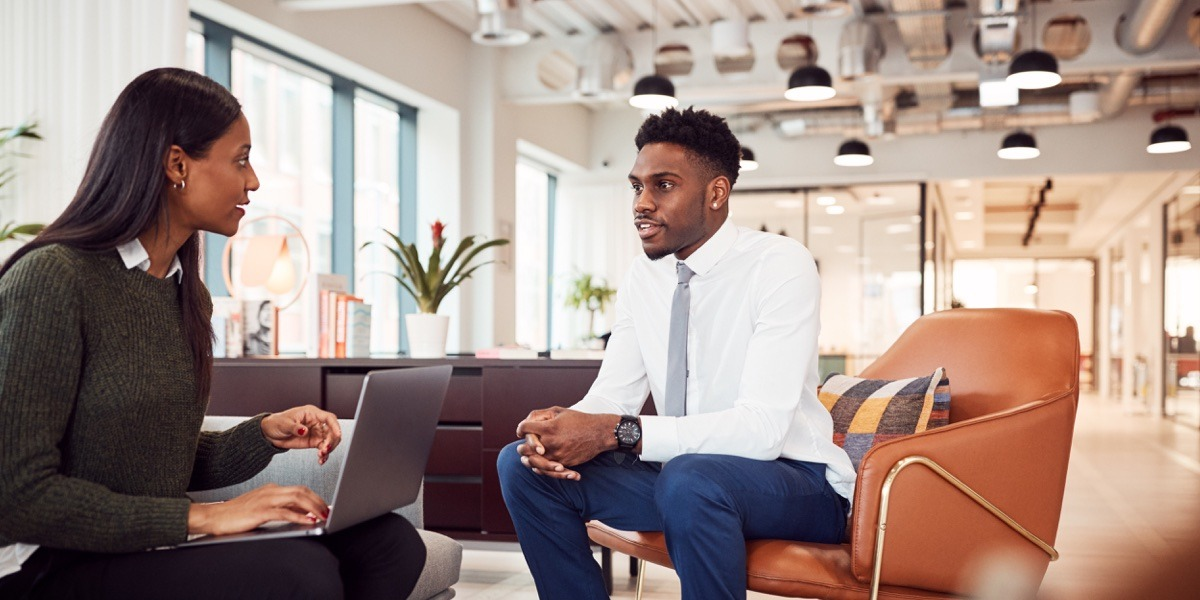 A UX researcher being interviewed by a hiring manager in a comfortable office environment