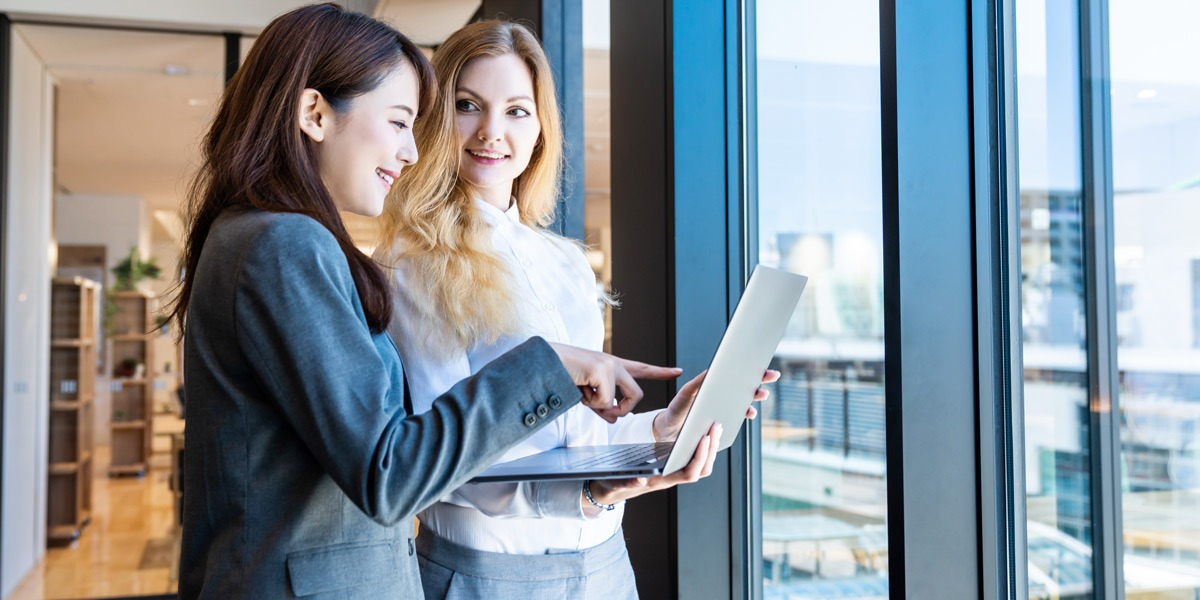 Two data analysts standing by a window, looking at a laptop